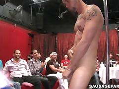 Salacious gay stripper in a bar lets the clients suck his wang
