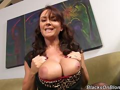 Busty cougar in nylons puts her huge fake tits on display