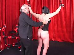 Spread-eagled shackled woman in leather mask and hood gets caned on her ass