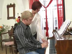 Older redhead piano teacher gives free lessons to her sexy student