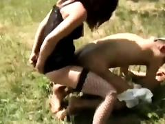 Milf in stockings fucks a guy with a strap-on in nature