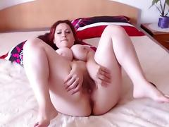 Chubby redhead shows off her big tits and masturbates in be