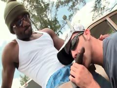 Outdoor gay BJ scene with black and white studs