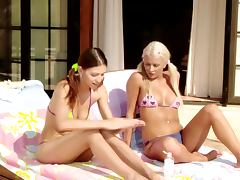 Two luscious babes start fisting each other while getting suntan