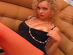 Curly hair blonde cutie in orange fishnets