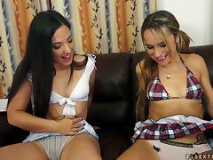 Three beautiful lesbians share a vibrator on a sofa