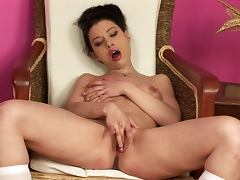 Sexy brunette babe sits on an armchair toying her pussy