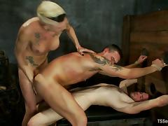 Two guys get fucked by a horny short-haired shemale in BDSM scene