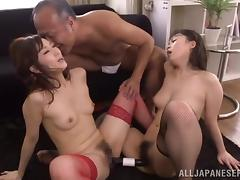 Two Asian girls in fishnets lick and toy their pussies