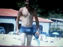 hot guy walking on beach rubbing his bulge