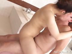 Sex hungry Asian MILF gives a massage and rides a dick