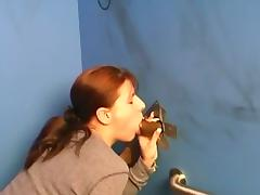 Redhead sucks a big cock out of a glory hole