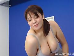 A sporty Japanese girl with big boobs gives a titjob in a gym