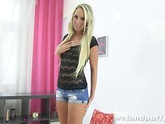 A long-haired blonde toys her pussy with big dildos