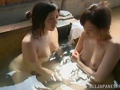 Two horny Japanese lesbians make out and pet each other in a sauna