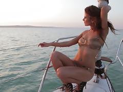 Sexy brunette shows off her sexy body while sailing on a boat